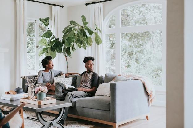 Couple africain se détendre dans un salon à la maison