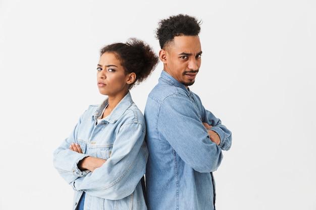 Couple africain sérieux dans des chemises en denim debout dos à l'autre avec les bras croisés tandis que sur un mur gris