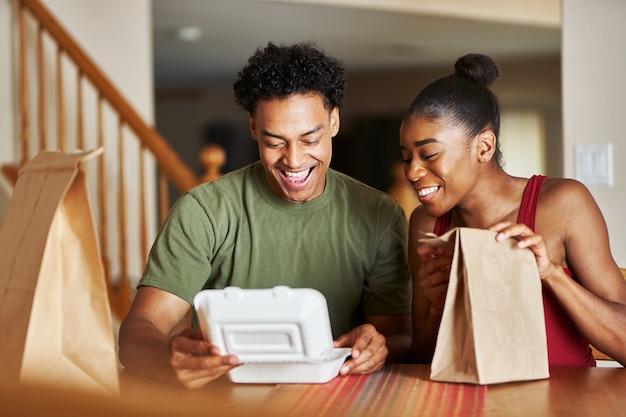 Couple afro-américain assis à table en regardant la livraison de nourriture