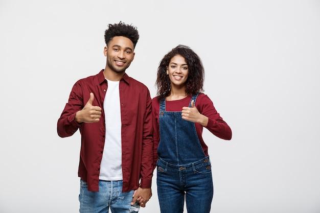 Couple afro-américain attrayant montrant le pouce vers le haut sur fond de studio blanc.
