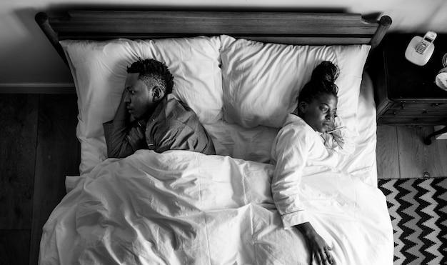Couple afro-américain dormir dos à dos