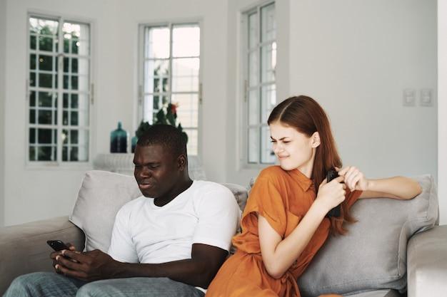 Couple afro-américain et femme blanche avec des téléphones, querelle de famille