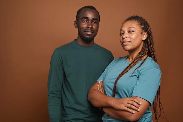 Couple afro-américain moderne posant avec confiance sur brun
