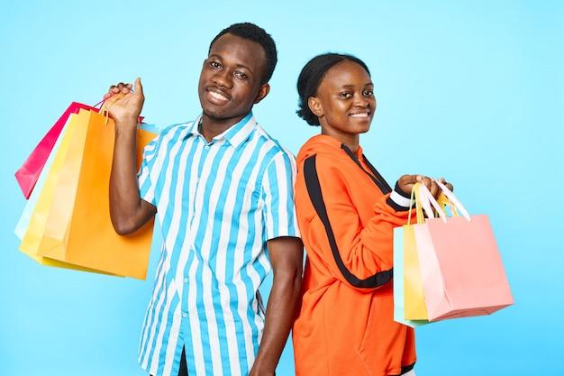 Couple afro-américain posant avec des sacs à provisions