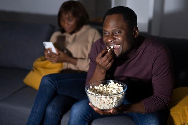 Couple afro-américain regardant netflix ensemble à la maison