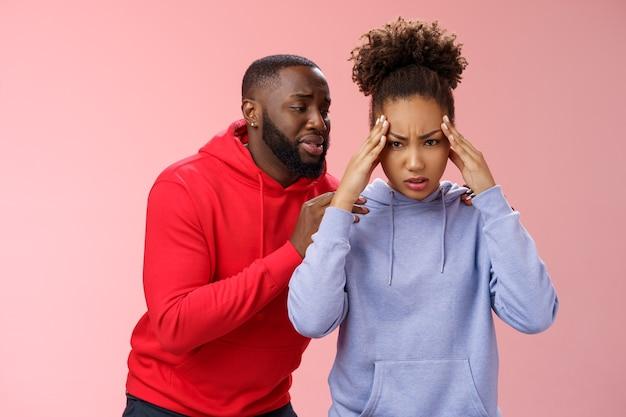 Un couple afro-américain s'est battu en se disputant une femme marre ne peut plus entendre s'excuser se tenir la main les temples en fronçant les sourcils sous la pression d'un homme agacé implorant le pardon derrière le dos suppliant de s'excuser