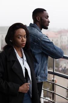 Couple afro-américain sérieux posant sur balcon