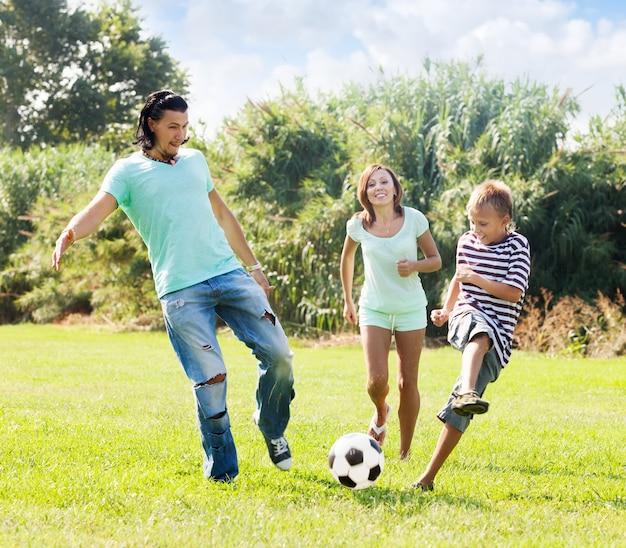 Couple d'âge moyen et adolescent jouant au ballon de football