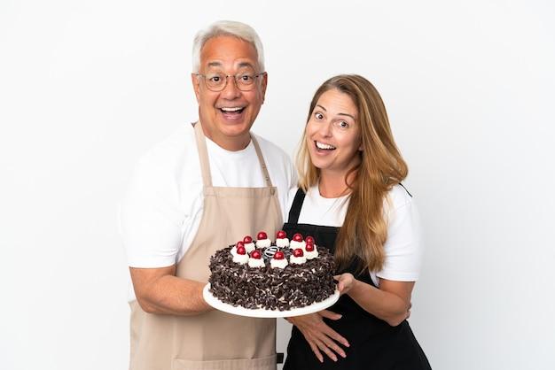 Couple d'âge moyen chef tenant un gâteau d'anniversaire isolé sur fond blanc