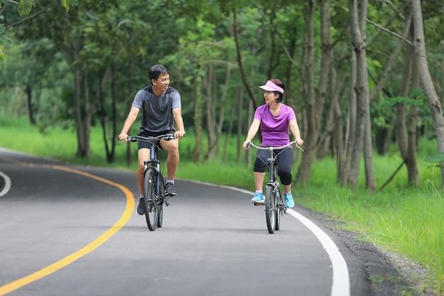 Couple d'âge moyen exercice de détente avec vélo dans le parc