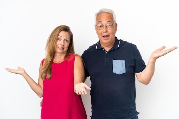 Couple d'âge moyen isolé sur fond blanc ayant des doutes et avec une expression de visage confuse