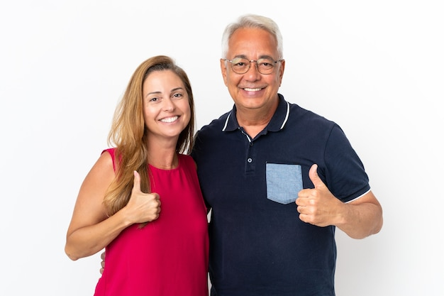 Couple d'âge moyen isolé sur fond blanc donnant le geste du pouce vers le haut