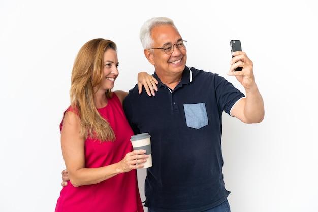 Couple d'âge moyen isolé sur fond blanc faisant un selfie avec le mobile