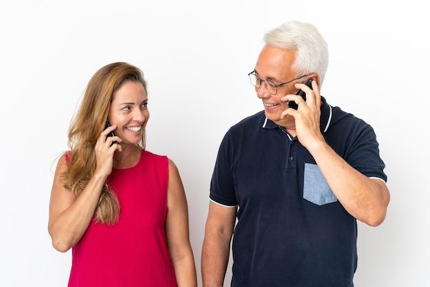 Couple d'âge moyen isolé sur fond blanc, parler au mobile