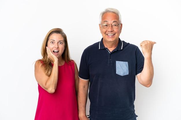 Couple d'âge moyen isolé sur fond blanc, pointant le doigt sur le côté et présentant un produit
