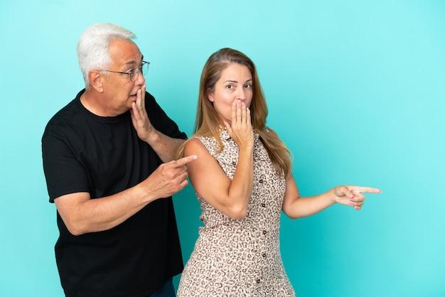 Couple d'âge moyen isolé sur fond bleu doigt pointé sur le côté avec un visage surpris