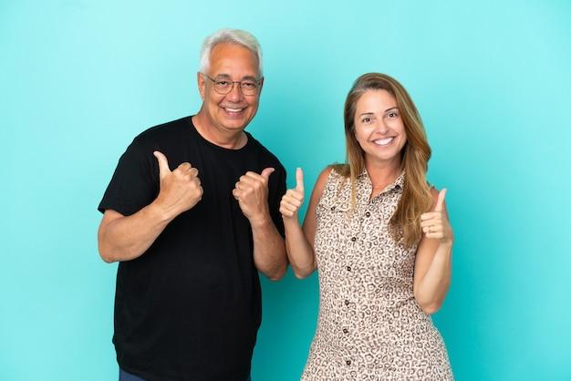 Couple d'âge moyen isolé sur fond bleu donnant un coup de pouce geste avec les deux mains et souriant