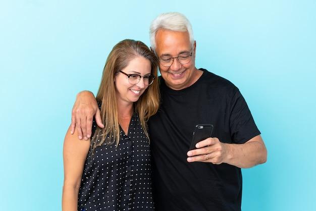 Couple d'âge moyen isolé sur fond bleu envoyant un message ou un e-mail avec le mobile