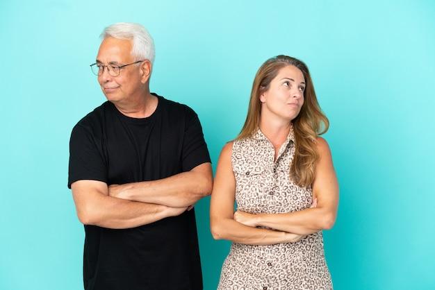 Couple d'âge moyen isolé sur fond bleu avec une expression de visage confuse tout en mordant la lèvre