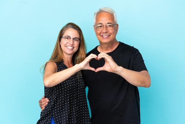Couple d'âge moyen isolé sur fond bleu faisant un coeur avec les mains