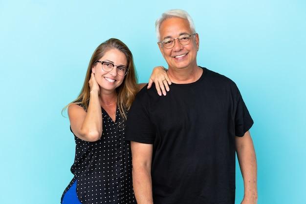 Couple d'âge moyen isolé sur fond bleu heureux et riant