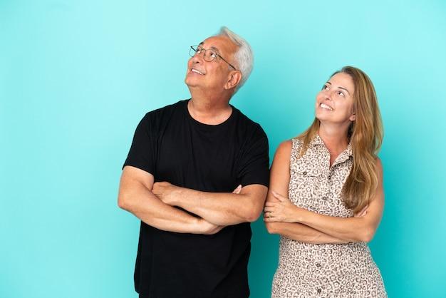 Couple d'âge moyen isolé sur fond bleu en levant tout en souriant