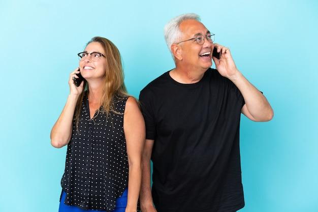 Couple d'âge moyen isolé sur fond bleu parlant au mobile