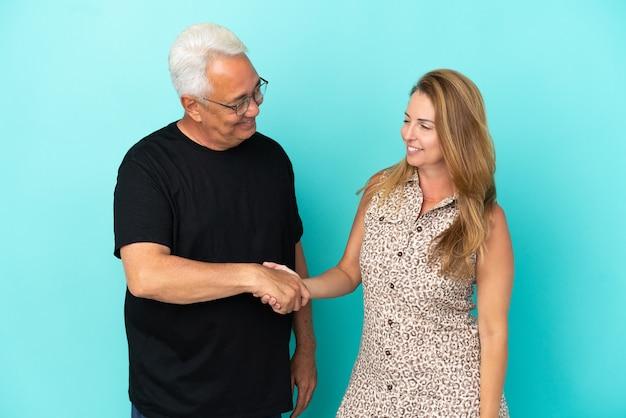 Couple d'âge moyen isolé sur fond bleu poignée de main après une bonne affaire