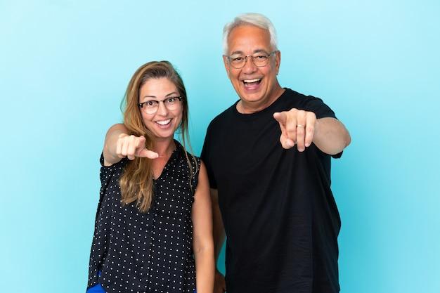 Couple d'âge moyen isolé sur fond bleu pointe le doigt vers l'avant
