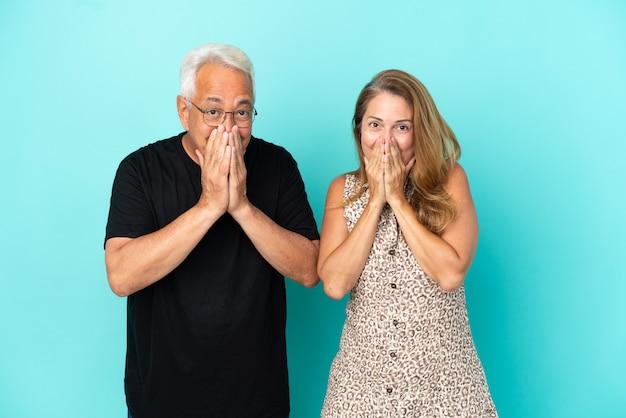 Couple d'âge moyen isolé sur fond bleu souriant beaucoup tout en couvrant la bouche