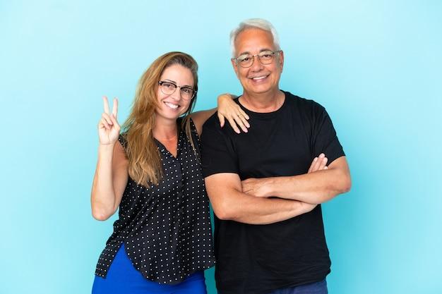 Couple d'âge moyen isolé sur fond bleu souriant et montrant le signe de la victoire