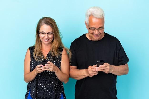 Couple d'âge moyen isolé sur fond bleu surpris et envoyant un message ou un e-mail avec le mobile