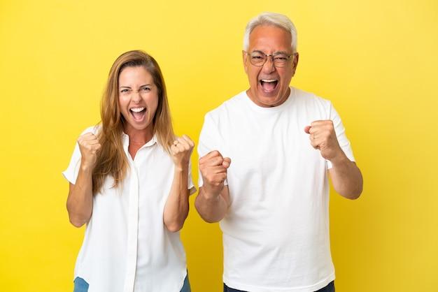Couple d'âge moyen isolé sur fond jaune célébrant une victoire