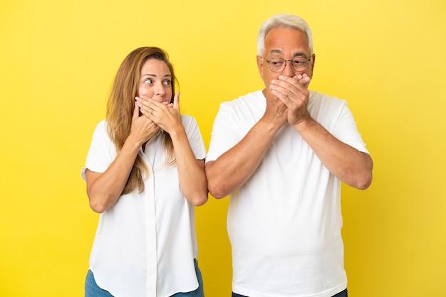 Couple d'âge moyen isolé sur fond jaune couvrant la bouche avec les mains