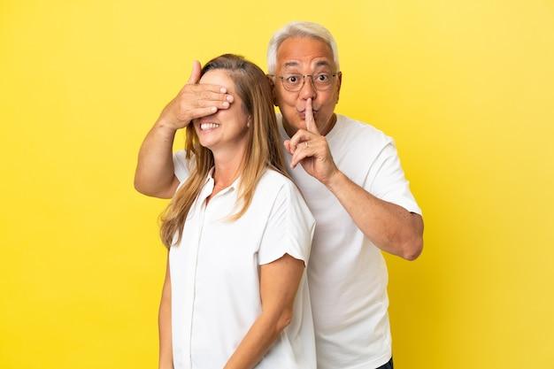 Couple d'âge moyen isolé sur fond jaune couvrant ses yeux pour la surprendre
