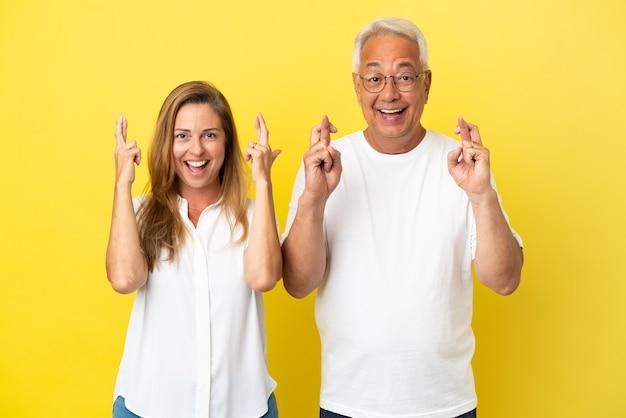 Couple d'âge moyen isolé sur fond jaune avec croisement de doigts