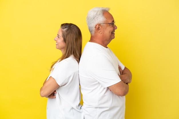 Couple d'âge moyen isolé sur fond jaune en gardant les bras croisés