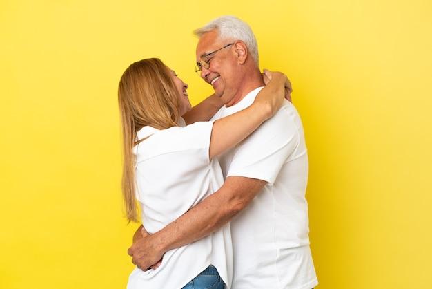 Couple d'âge moyen isolé sur fond jaune hugging