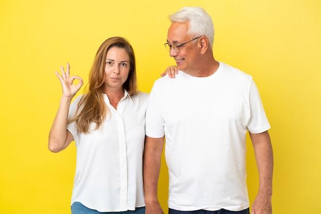 Couple d'âge moyen isolé sur fond jaune montrant un signe ok avec les doigts