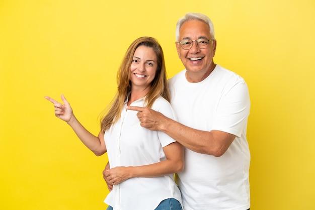 Couple d'âge moyen isolé sur fond jaune, pointant le doigt sur le côté et présentant un produit