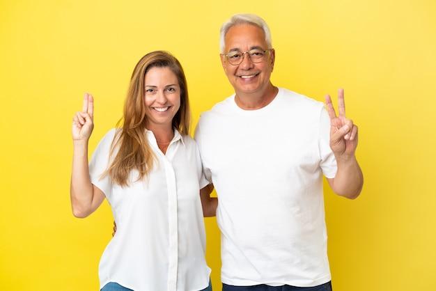 Couple d'âge moyen isolé sur fond jaune souriant et montrant le signe de la victoire