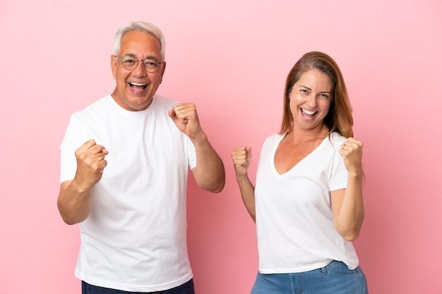 Couple d'âge moyen isolé sur fond rose célébrant une victoire en position de vainqueur