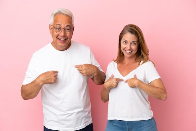 Couple d'âge moyen isolé sur fond rose avec une expression faciale surprise