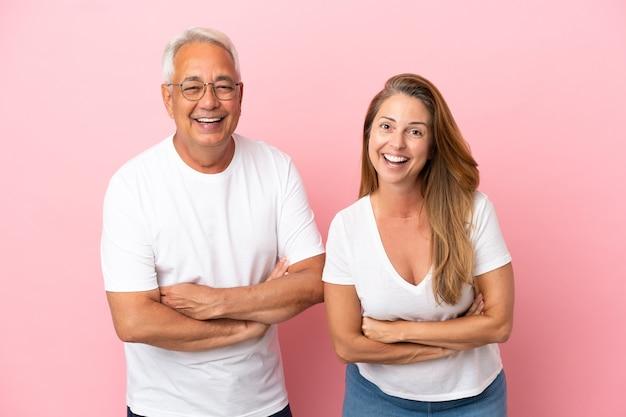 Couple d'âge moyen isolé sur fond rose en gardant les bras croisés en souriant