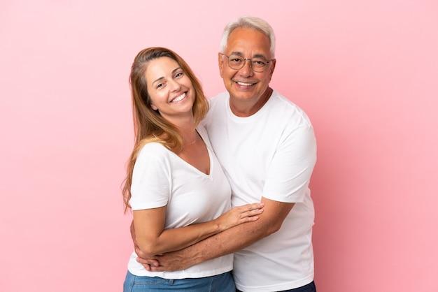 Couple d'âge moyen isolé sur fond rose hugging