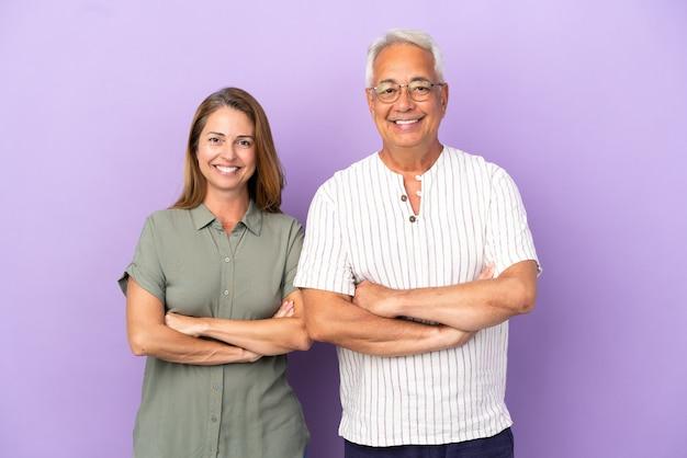 Couple d'âge moyen isolé sur fond violet en gardant les bras croisés