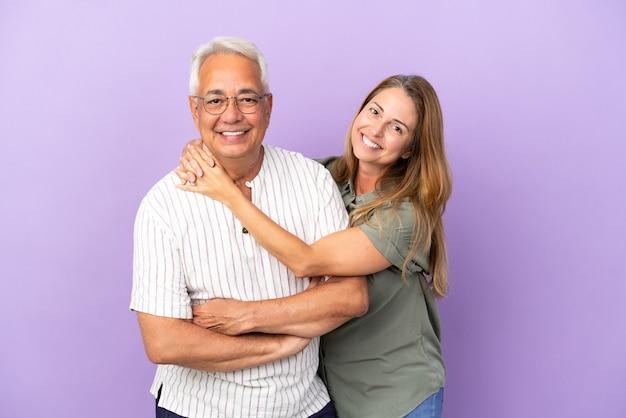 Couple d'âge moyen isolé sur fond violet serrant