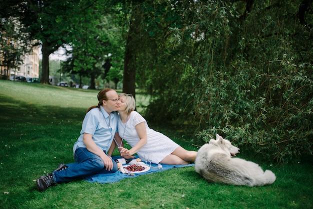 Couple d'âge moyen avec leur animal de compagnie au pique-nique
