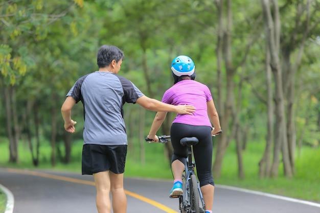 Couple d'âge moyen marchant avec leur vélo dans le parc