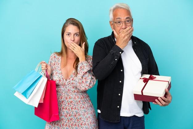 Couple d'âge moyen avec panier et cadeau isolé sur fond bleu couvrant la bouche avec les mains pour avoir dit quelque chose d'inapproprié